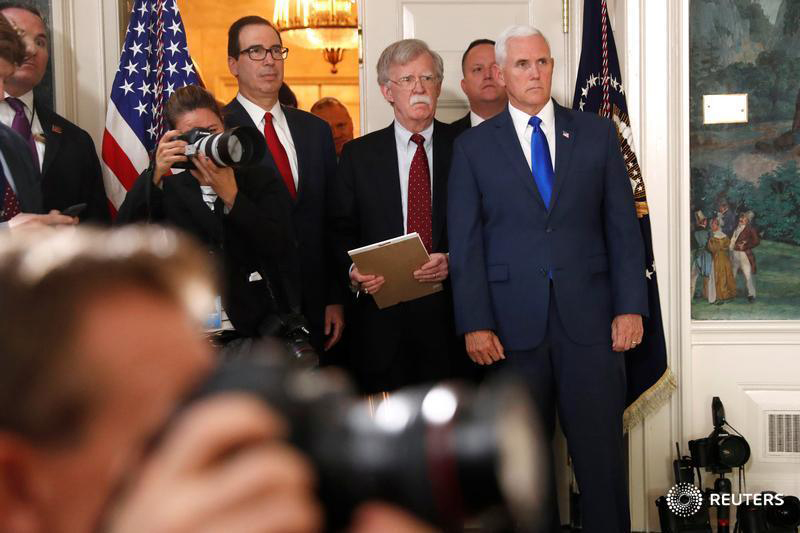 U.S. Treasury Secretary Steven Mnuchin, National Security Advisor John Bolton and Vice President Mike Pence listen as President Donald Trump announces his intention to withdraw from the JCPOA Iran nuclear agreement during a statement in the Diplomatic Room at the White House in Washington, U.S. May 8, 2018. Photography: Jonathan Ernst