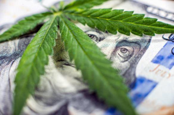 Cannabis leaf on top of a new 100 dollar bill
