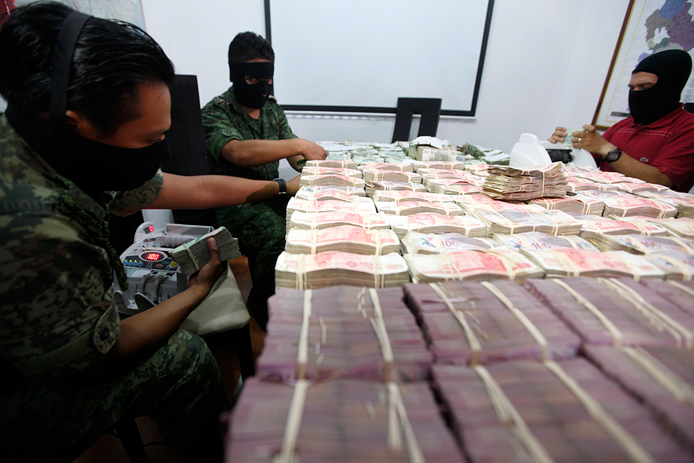 Military officers count money seized during an operation at a military zone on the outskirts of Monterrey, Mexico. Photography: REUTERS/Tomas Bravo. Bribery and corruption: Know your ABC