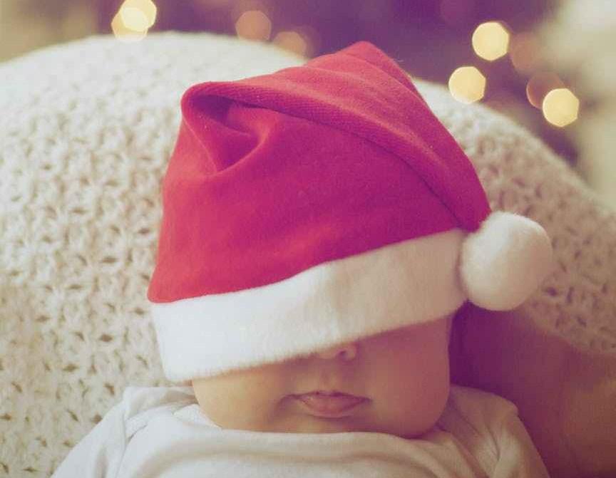 close up of illuminated christmas tree and a baby