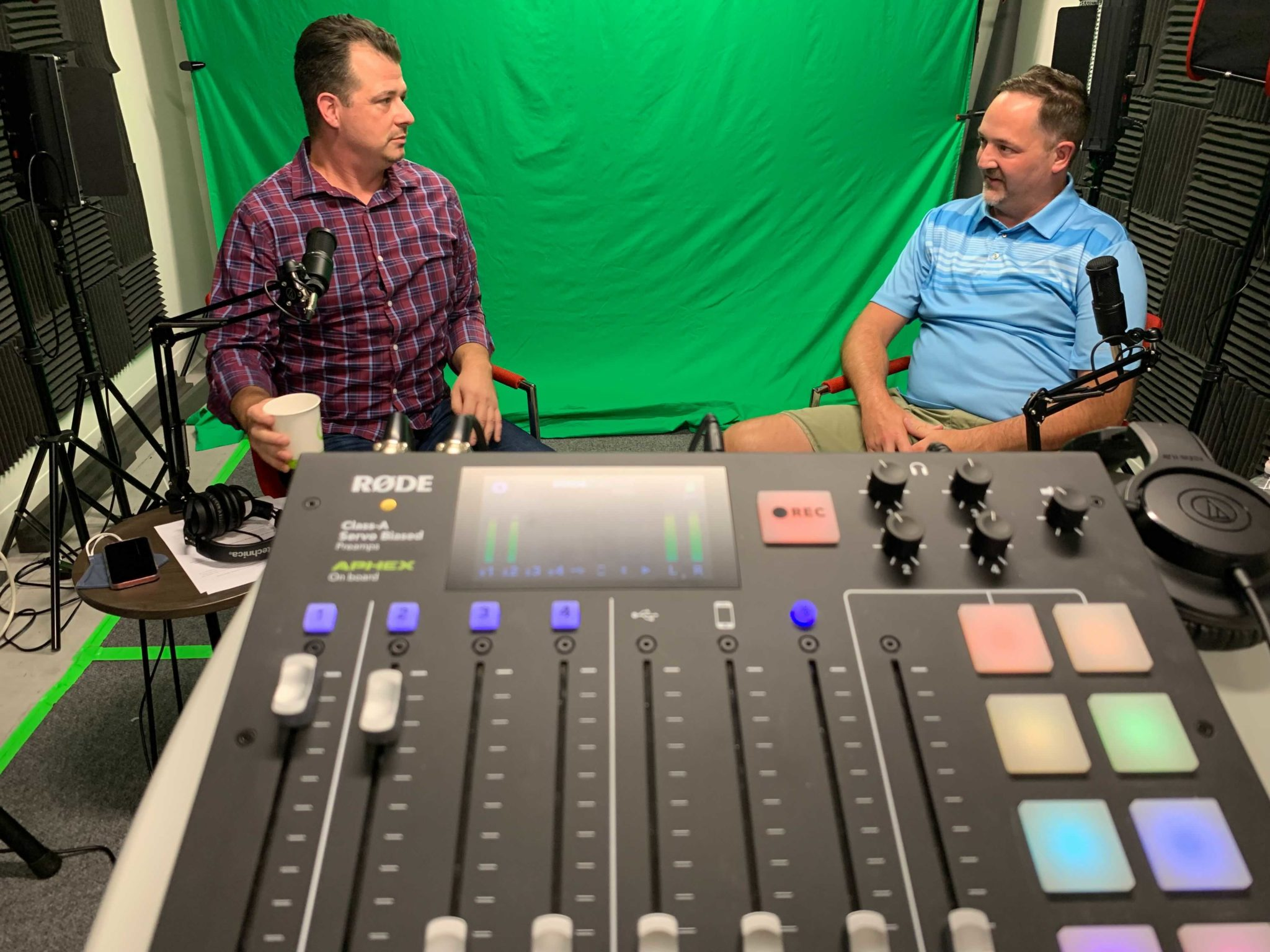In the foreground sits a Rode podcast recorder, with guests Jason Ward and Scott Sendelweck in front of a green screen. Jason is white male in his 40's with brown hair, wearing a plaid button down shirt. Scott Sendelweck is also a white male in his 40's with brown hair and a goatee, wearing a blue striped polo and khaki shorts.