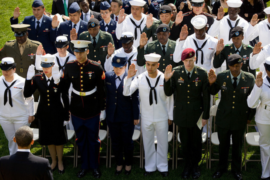 President Barack Obama, lower left, looks on as 24 active duty service members take an oath during a naturalization ceremony in the Rose Garden at the