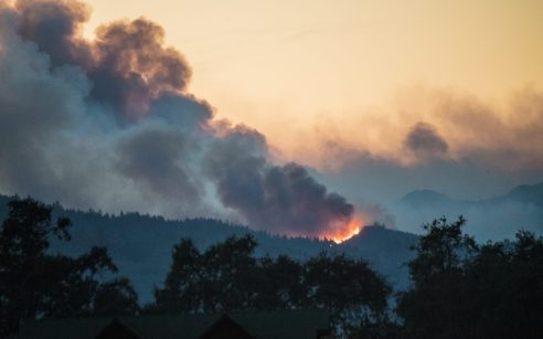 Smoke and flames of the Nuns Fire are seen one hill east of Oakville, seen from Napa, California.
